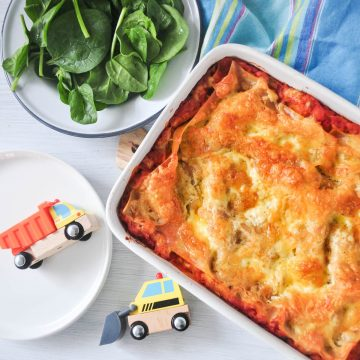 cheese and tomato lasagna in white baking dish with spinach salad and toy lorries on left hand side