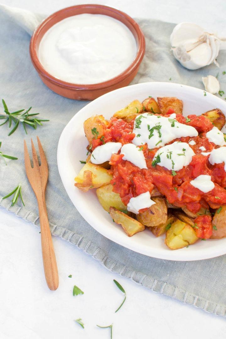 angled shot of patatas bravas with spanish terracotta dish of garlic aioli behind