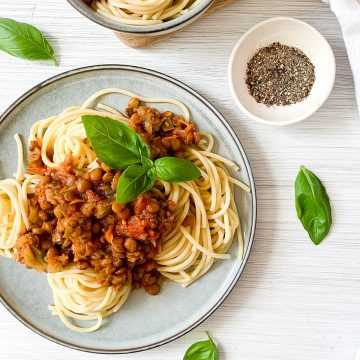 lentil bolognese on spaghetti in blue plate topped with fresh basil