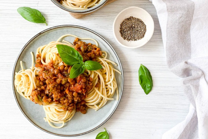 blue plate topped with lentil bolognese to the left of the image, fresh basil leaves and black pepper to the right