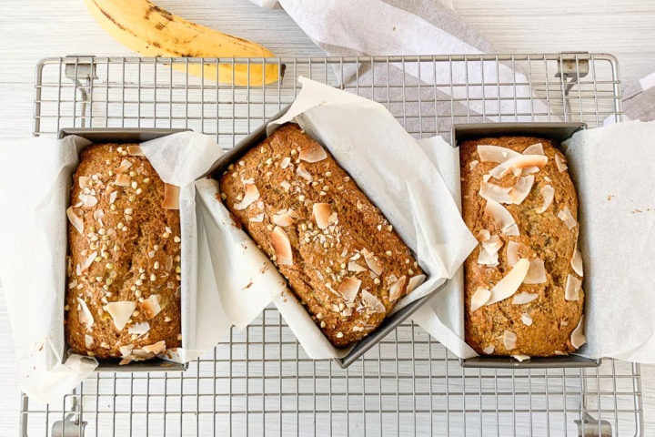 three loaves of baked banana bread in a row on cooling rack