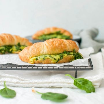 side view of croissant filled with spinach and cheese on cooling rack