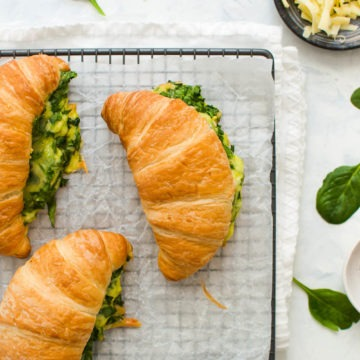 three spinach and cheese croissants on cooling tray