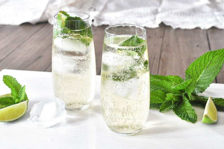 side view of two glasses filled with hugo cocktail on white dish with ice, lime and mint