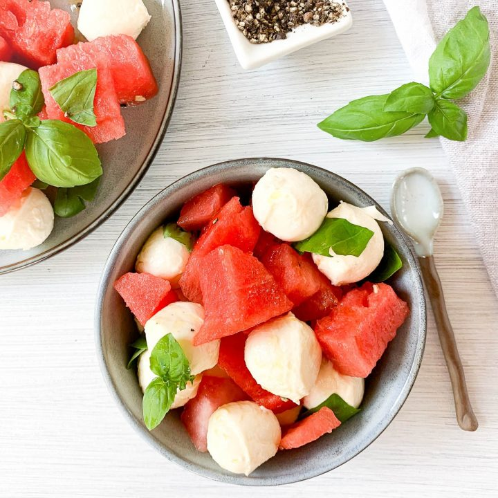 blue bowl of watermelon and mozzarella salad topped with fresh basil leaves and blue spoon to the right