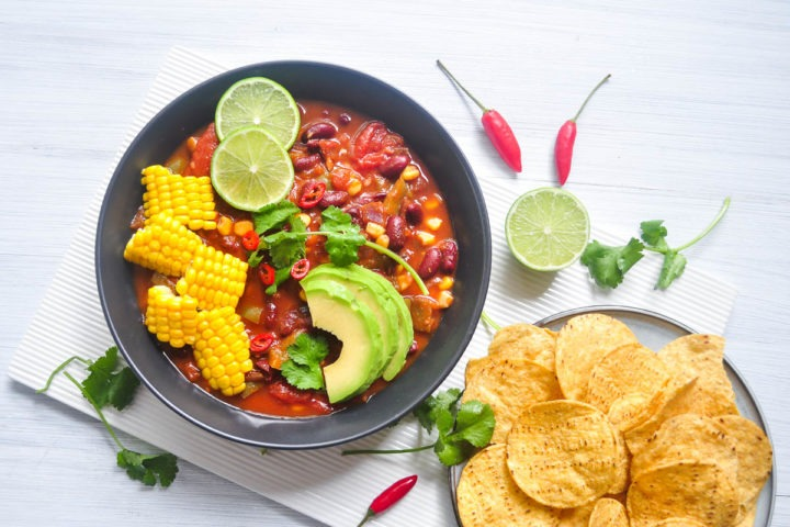 bowl of bean chilli topped with avocado slices, corn and lime and served with corn chips to the right