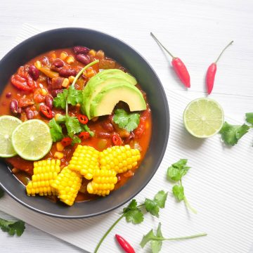 black bowl of Mexican bean chilli toped with slices corn cob, avocado and fresh coriander