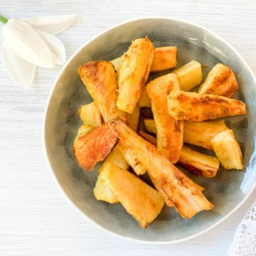 spiced roast parsnips on blue plate with white flower top left corner