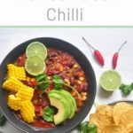 black bowl of vegetarian bean chilli woth lime, corn and corn chips
