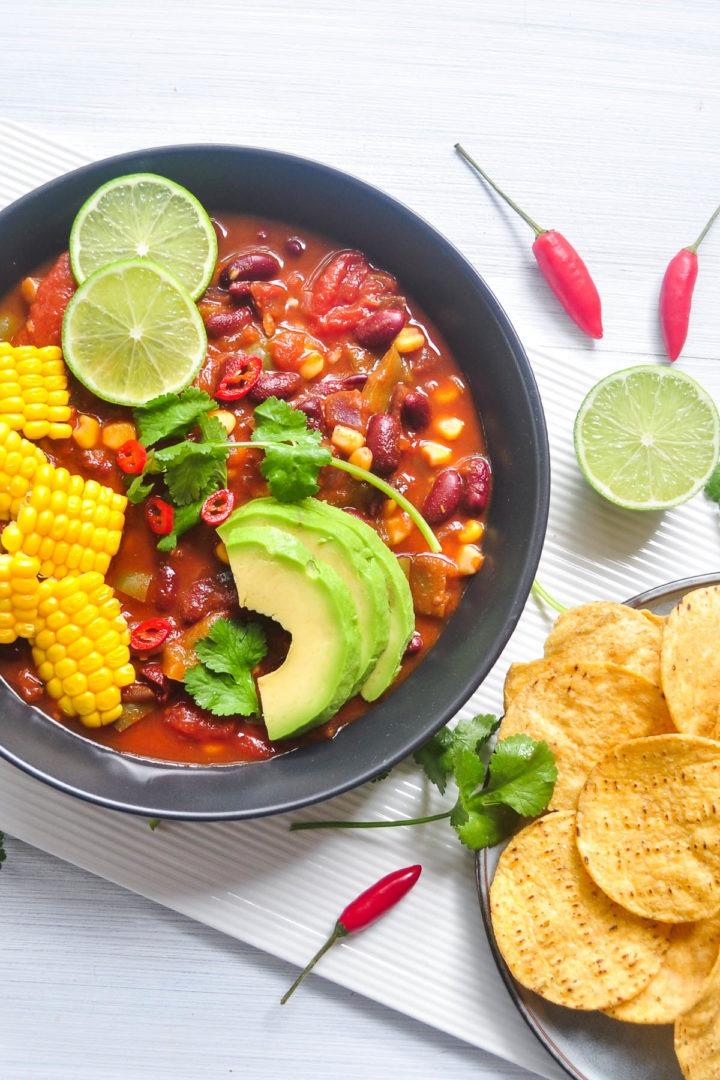 bean chilli to left of image with tortilla corn chips to the right, fresh coriander and red chillis sprinkled over the top