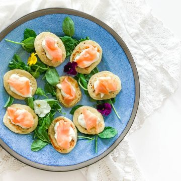 blinis topped with smoked salmon on blue plate to the left of the image
