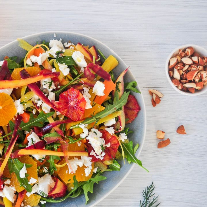 sliced blood oranfes, shaved heirloom carrots and rocket and feta with chopped almonds to the right of the image