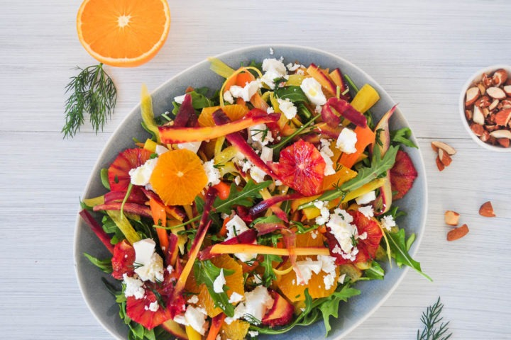 sliced oranges and blood oranges with feta, rocket and carrot strips on blue plate with orange slices, dill and almonds around the plate