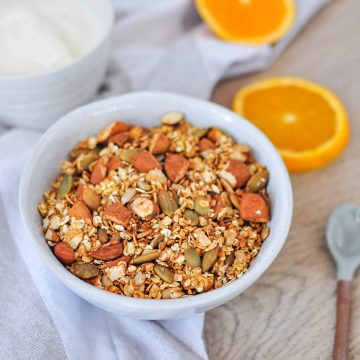 bowl of granola with nuts and seeds with sliced orange in the background