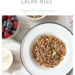no added sugar healthy granola with cacao nibs in white bowl served with bowls or berries and plain yogurt to the left