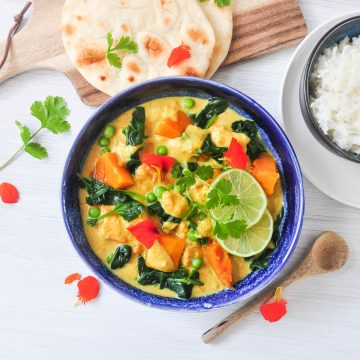 pumpkin satay curry in blue bowl topped with edible orange flower petals, lime slices and fresh coriandar