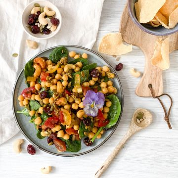 blue plate filled with Indian spiced chickpea salad with mini popadoms to the right