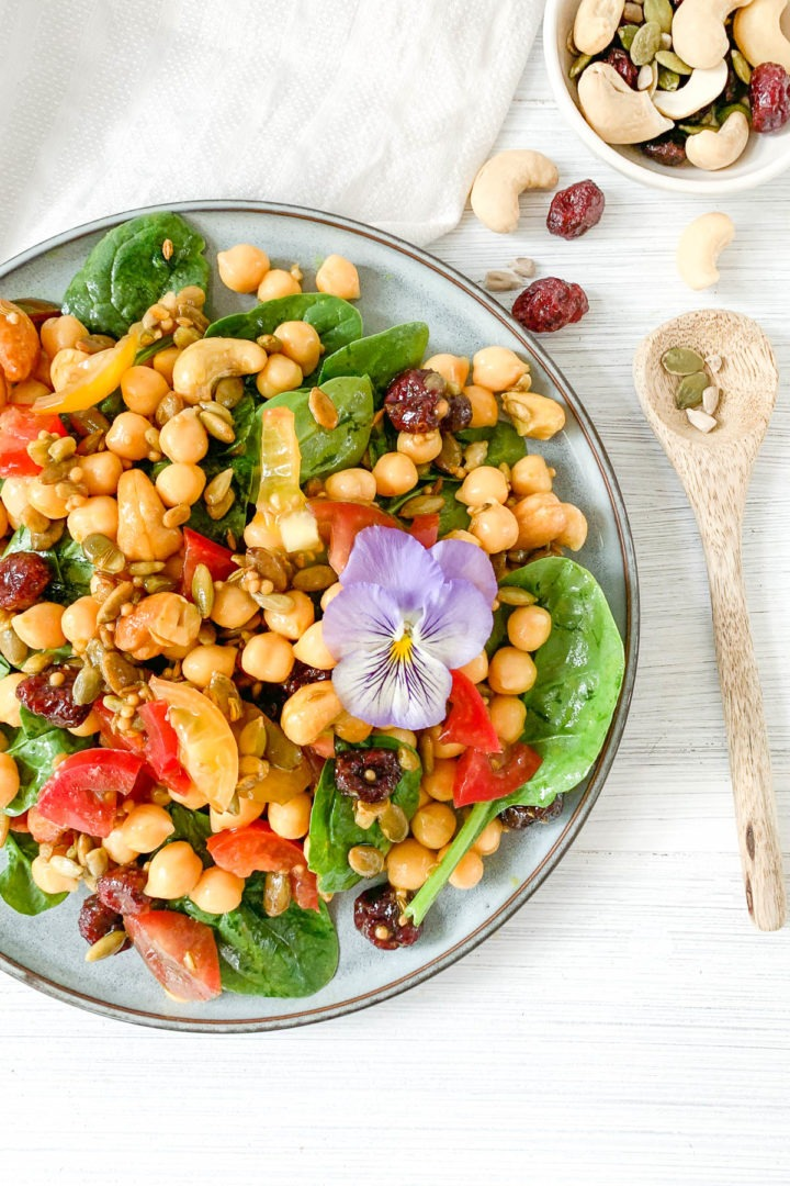plate of chickpea salad with extra nuts, seeds and dried cranberries in bowl to the top right corner to sprinkle over