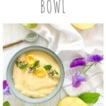 mango lassie smoothie bowl with lime slices, mango pieces and mint leaves scattered around the bowl on a white background