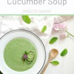 white bowl full of green cucumber soup topped with sliced cucumber and chive flower