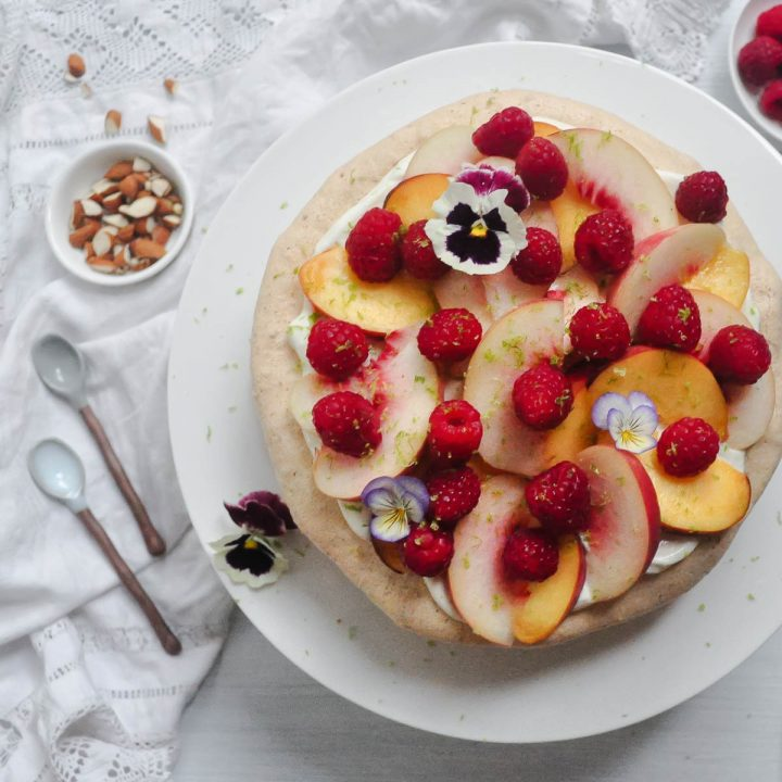 peach melba almond meringue gateau on white plate topped with fresh raspberries, peach slices and edible flowers