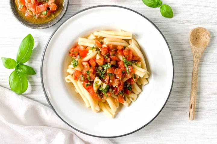 sauce vierge on pasta in white bowl on white background with fresh basil leaves