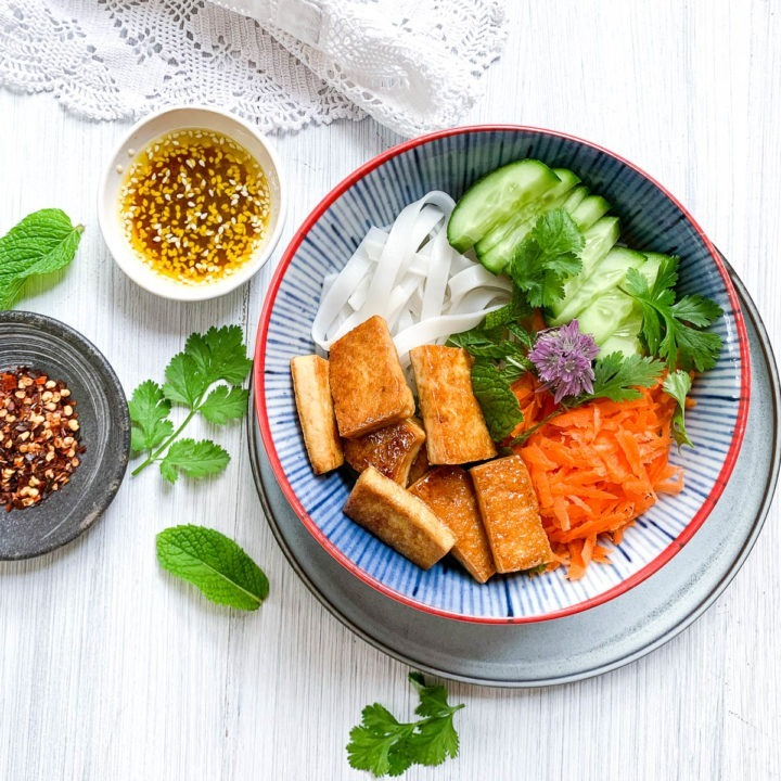 sticky tofu and noodle salad in blue striped bowl on white background with fresh herbs and dried chilis