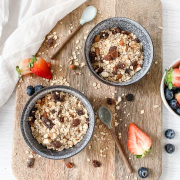 two bowls of muesli on wooden board with blueberries and strawberries scattered around