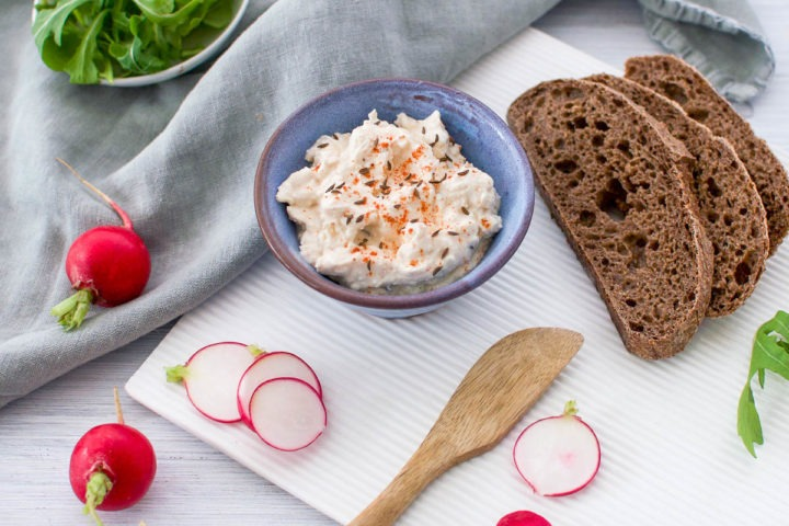 small blue bowl with korozott served with dark rye bread and radishes