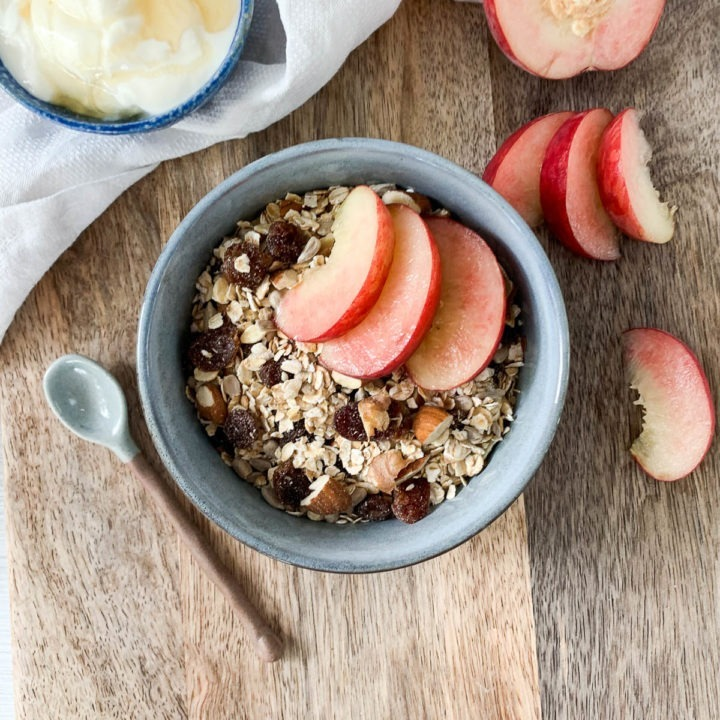 muesli served with fresh peach slices and yogurt drizzled with honey