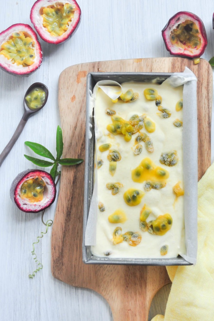 vertical image of passionfruit ice cream in rectangle tin with passionfruit halves surrounding it