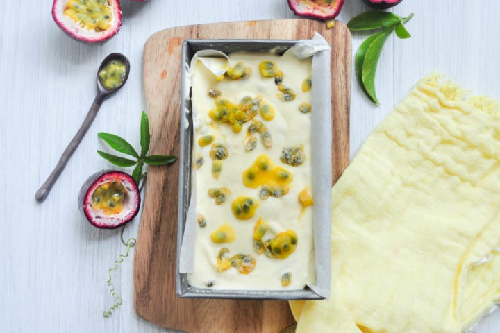 tin of passionfruit ice cream on wooden board with passionfruit pulp drizzled over the top
