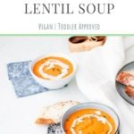 bowls of carrot and red lentil soup swirled with coconut milk and served with bread