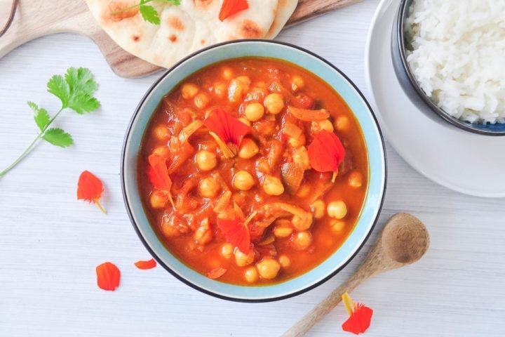 bowl of chana masala with rice and naan bread