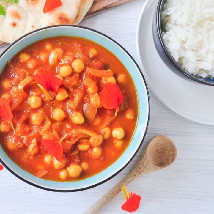 chana masala decorated with red edible flower petals served with rice