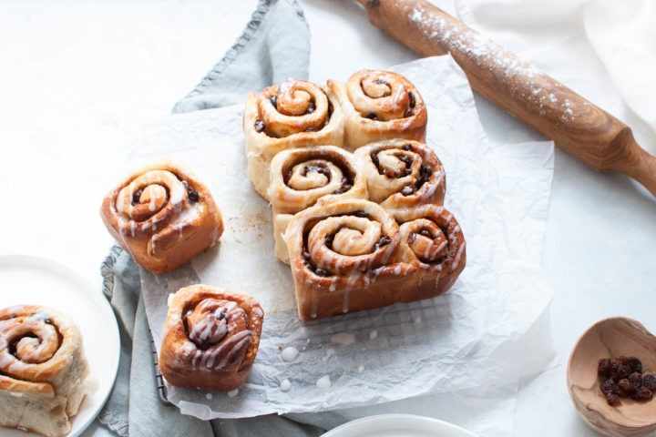 chelsea buns on rack, one one white plate to the left