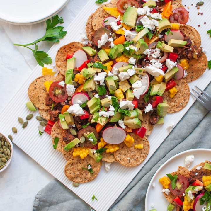vegetarian nachos on white serving platter with pumpkin seeds scattered over the nachos and table
