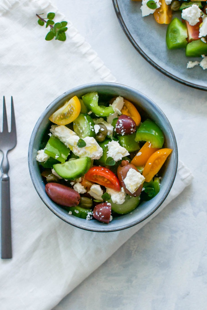 blue bowl of greek salad with plate of salad just visible