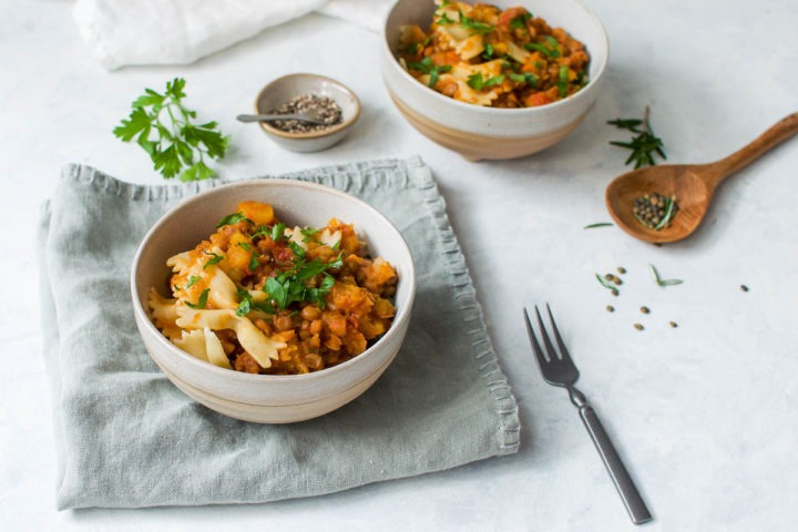 two bowls of lentil and butternut ragu sprinkled with parsley, with green lentils in the background
