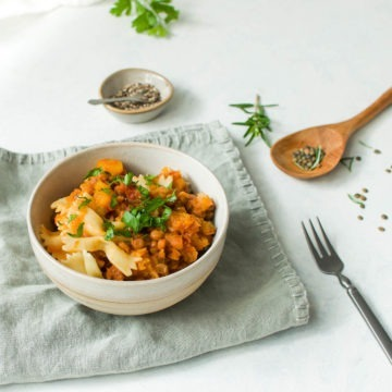 bowl of butternut and lentil ragu on a bowl of bow pasta shapes with fresh rosemary and uncooked lentils in background