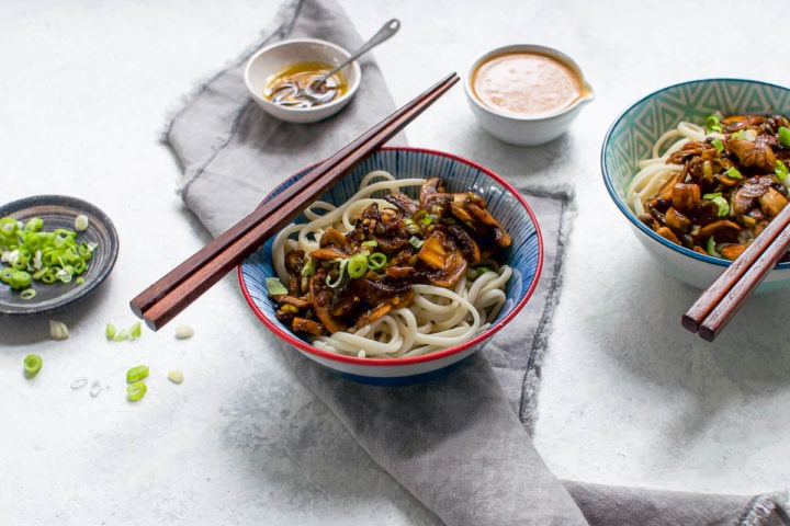 two bowls of dan dan noodles with spiced mushrooms leaving noodles visible, bowls of chilli oil and peanut sauce in the background