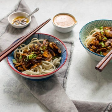 Two bowls of dan dan noodles with a layer of mushrooms on the noodles, the spicy chilli oil in a seperate bowl