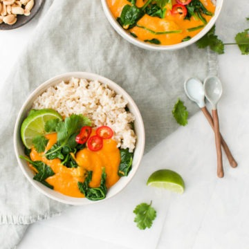 African peanut stew in bowls served with rice and topped with lime and fresh red chilli