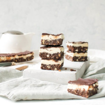 Three Nanaimo bars stacked on top of each other with a teapot in the background