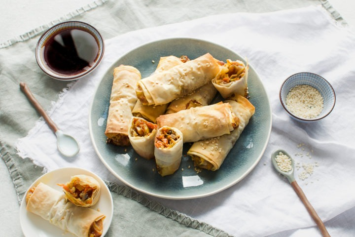 baked Japanese spring rolls on blue plate with two on a small side plate to the left