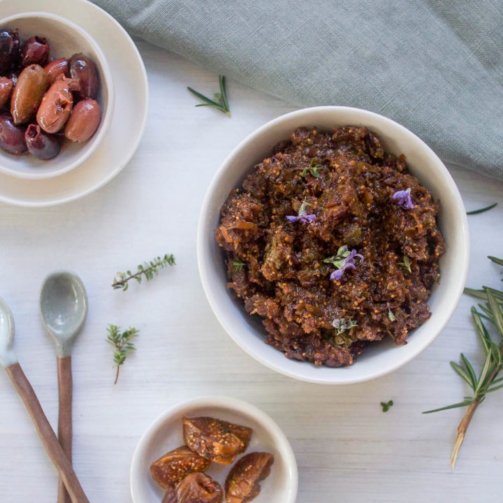 bowl of black olive tapenade decorated with purple rosemary flowers with olives and dried figs in bowls to the side