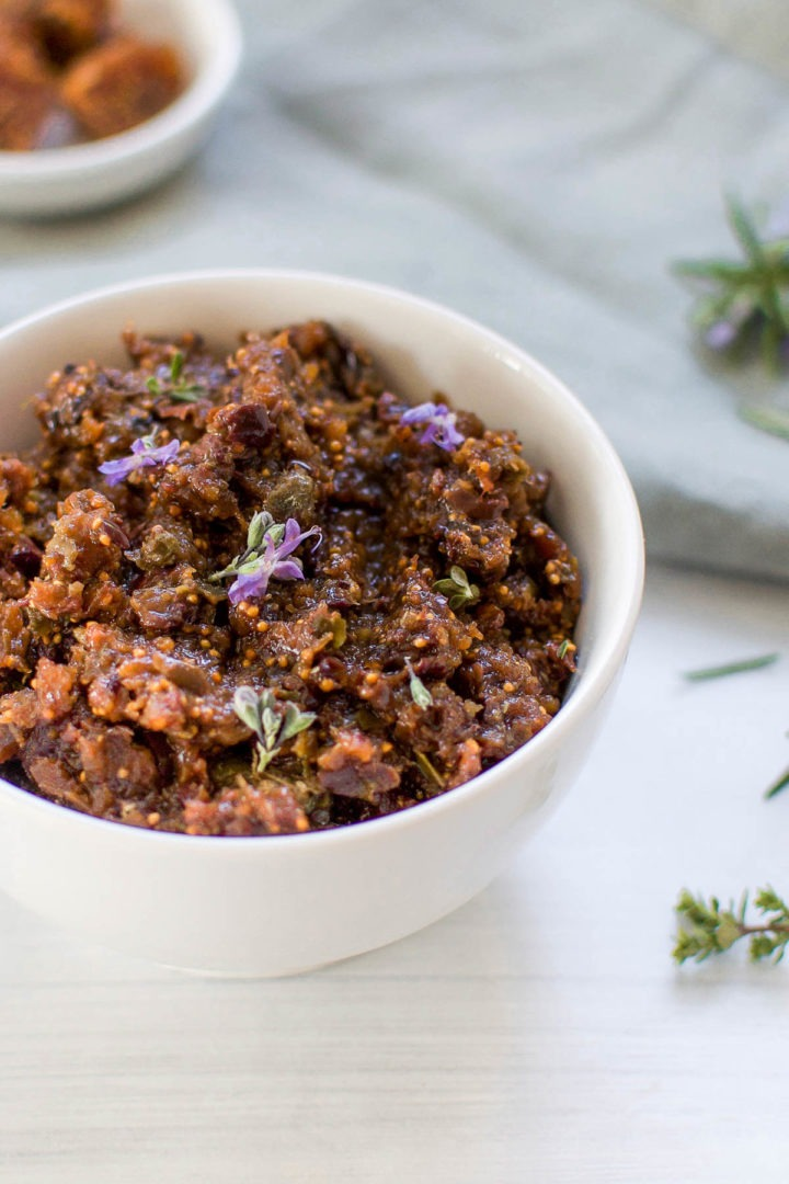long image of black olive tapenade in white bowl topped with purple rosemary flowers