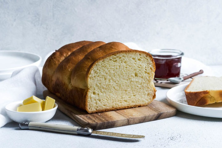 cut bread to see the fluffy interior of the loaf. A pot of jam in the background