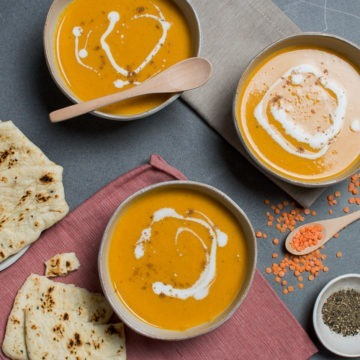 Three bowls of Mulligatawny soup with flat bread