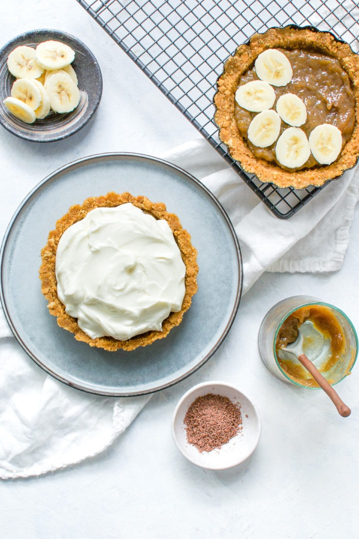 long image of two banoffee pies, on with yogurt on and the other banana jam and sliced bananas